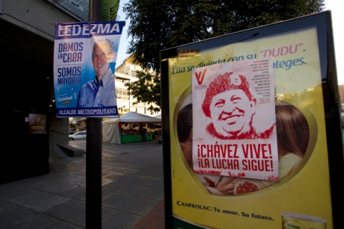 Rare opposition campaign sign, matched by poster advertising the Great Housing Mission of Venezuela as evidence that Chávez's dream is alive.